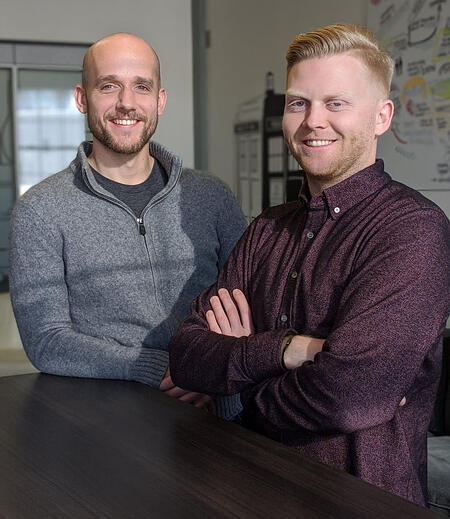 two men stand smiling towards the camera in front of a tall desk